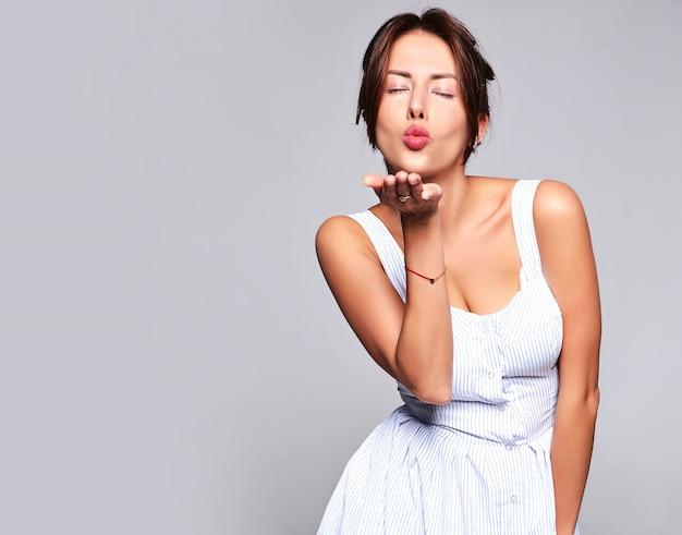 Portret mooie schattige brunette vrouw model in casual zomerjurk zonder make-up geïsoleerd op grijs. een kus geven