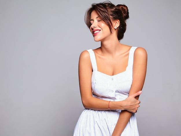 Portret mooie schattige lachende brunette vrouw model in casual zomerjurk zonder make-up geïsoleerd op grijs