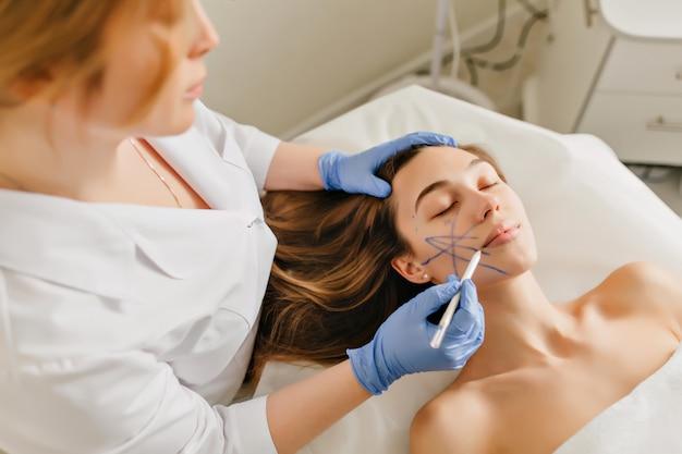 Portret mooie vrouw bij voorbereiding op verjonging, cosmetologie operatie in de schoonheidssalon. bekijk van bovenaf de handen van de arts in blauwe handschoenen puttend uit gezicht, botox, schoonheid