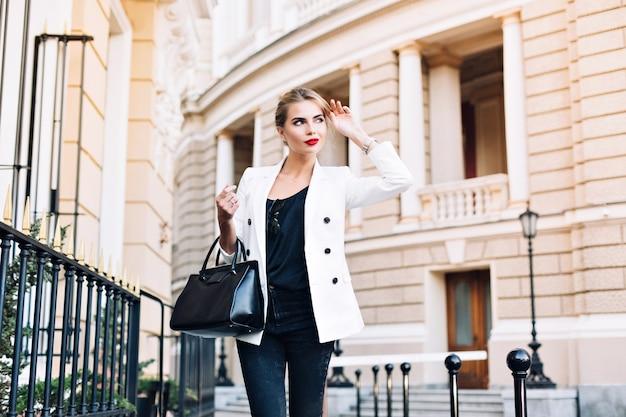 Portret mooie vrouw in witte jas lopen op straat. ze glimlacht naar haar kant.