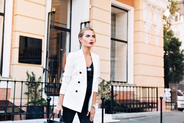 Portret mooie vrouw in witte jas op straat. ze kijkt naar de kant.