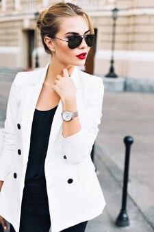 Portret mooie vrouw in zonnebril met rode lippen op straat. ze kijkt naar de kant.