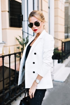 Portret mooie vrouw in zonnebril op straat. ze kijkt naar de camera.
