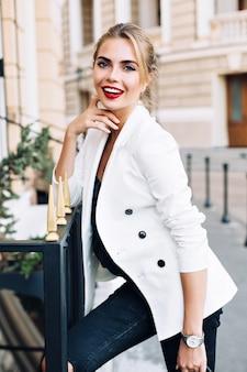 Portret mooie vrouw leunend op hek op straat. ze lacht naar de camera.