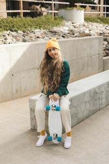 Portret mooie vrouw met ourdoor skateboard