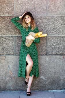 Portret mooie vrouw met stokbrood in handen die zich voordeed op de muur. vrouw gekleed in franse stijl