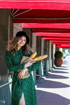 Portret mooie vrouw met stokbrood in handen op straat. vrouw gekleed in franse stijl