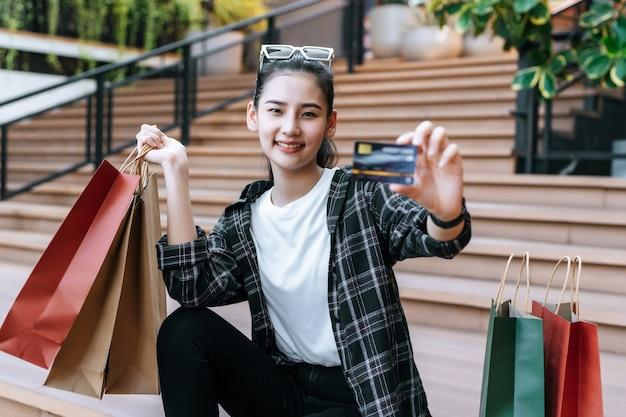 Portret mooie vrouw plaatst bril op hoofd met boodschappentas