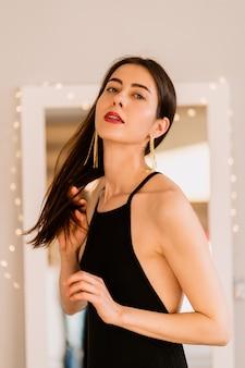 Portret mooie vrouw poseren in zwarte jurk