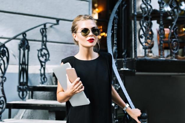 Portret mooie zakenvrouw in zwarte jurk op trappen buiten. ze kijkt naar de camera.