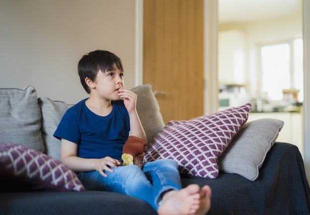 Portret nieuwe normale levensstijl kid zittend op de bank aardappelchips eten terwijl u tv kijkt