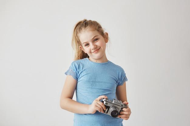 Portret o knap blond kind in blauw t-shirt glimlachen, staande met fotocamera in handen poseren voor schoolalbum.