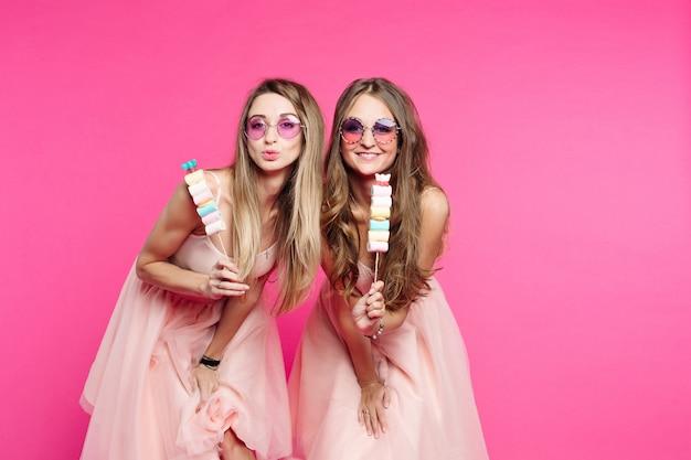 Portret o twee en lieve meisjes, in roze zonnebril en ziet eruit als prinsen of snoepjes, kus sturen naar de camera. vrouwen die marshmallows op stok tonen en plezier hebben. mode.
