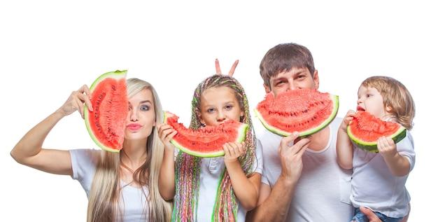 Portret oh gelukkig gezin met twee kinderen die watermeloenplakken voor hun gezichten houden die op wit worden geïsoleerd