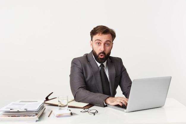 Portret omhoog van gekleed in een pak respectabele kantoormedewerker zittend op het bureaublad, recht in verwarring ongeloof kijkend, mond geopend van schokkend nieuws.