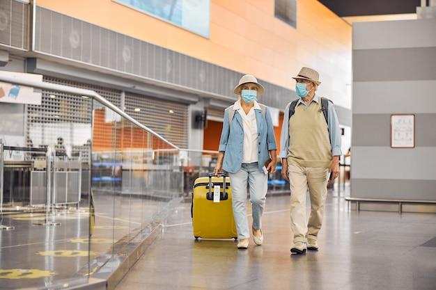 Portret op ware grootte van een oud toeristenpaar met instapkaarten die langs de luchthaventerminal gaan