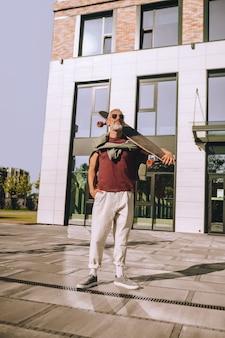 Portret op ware grootte van een skateboarder met het skateboard over zijn schouder voor een modern kantoorgebouw