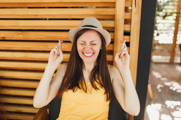 Portret opgewonden lachend jong meisje in stro zomerhoed, geel shirt met gekruiste vingers op houten muur in openlucht straat zomer coffeeshop café