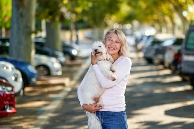 Portret oudere vrouw met een hond buitenshuis.