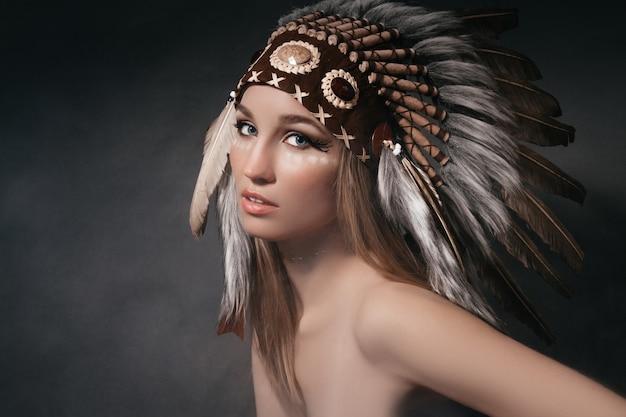 Portret perfecte vrouw in het gewaad van amerikaanse indianen in de rook op een grijze achtergrond. hoed gemaakt van veren. mysterieuze mystieke persoon, een sexy lichaam, een mooi gezicht