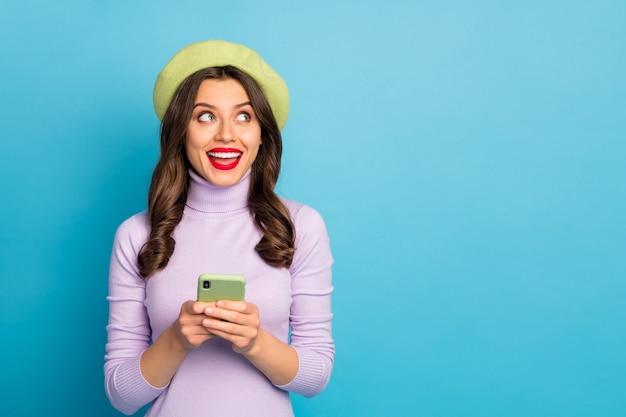Portret positief opgewonden meisje gebruik smartphone willen posten sociaal netwerk nieuws kijken copyspace genieten van gedachten schreeuwen slijtage stijl stijlvol trendy outfit rode lippen stok geïsoleerd blauwe kleur muur