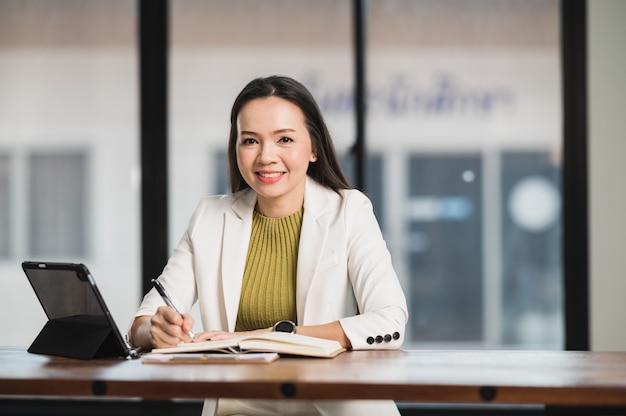 Portret professor leraar een aziatische vrouw van middelbare leeftijd zit in de klas aan de universiteit