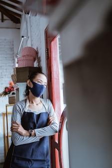 Portret saaie vrouw bloemist met schort en gezichtsmasker leunt op de deur op de ochtenddag
