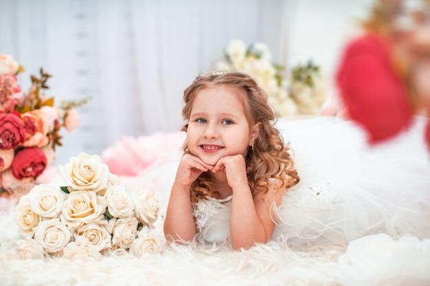 Portret schattig klein meisje in een mooie jurk met golvend, met een boeket rozen.