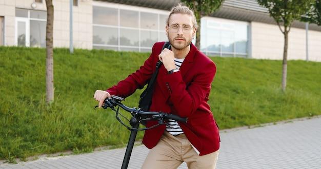 Portret shot van blanke knappe jongeman in rode jas en bril staan buiten met elektrische scooter en kijken naar camera. stijlvolle man bij voertuig op straat in de stad. knap mannelijk poseren.