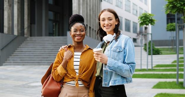 Portret shot van jonge mooie vrouwtjes van gemengd ras, beste vrienden glimlachend vrolijk naar camera met kopje koffie to-go en staan op straat in de stad. multi-etnische mooie gelukkige vrouwelijke studenten.