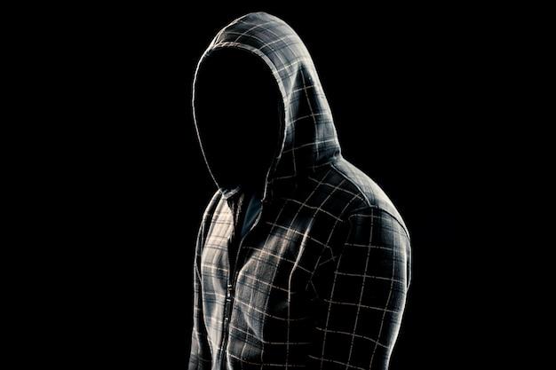 Portret, silhouet van een man in een kap op een zwarte achtergrond, zijn gezicht is niet zichtbaar.