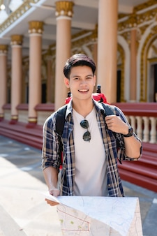 Portret smiley aziatische backpacker man met een papieren kaart in de hand bij prachtige thaise tempel