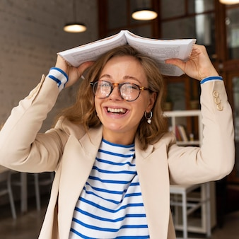 Portret smiley leraar met boek op hoofd