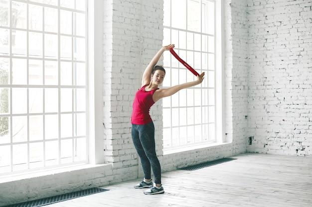 Portret sportieve aantrekkelijke jonge vrouw yoga student beginner in stijlvolle sportkleding asana's doen in ruime kamer zichzelf helpen met riem. mensen, sport, fitness, yoga, pilates en een actieve levensstijl