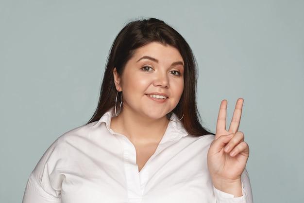 Portret stijlvolle gelukkig zelfverzekerde jonge vrouw met bochtige lichaam vredesteken tonen, overwinning gebaren met middelvinger en wijsvinger, vrolijk glimlachend. gevoelens, symbolen en houding