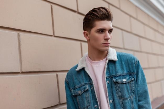 Portret stijlvolle jongeman in trendy blauwe jeugd casual jeans kleding in de buurt van vintage muur buiten in de stad. europese man in trendy kleding loopt op straat. nieuwe zomercollectie denimkleding voor heren.