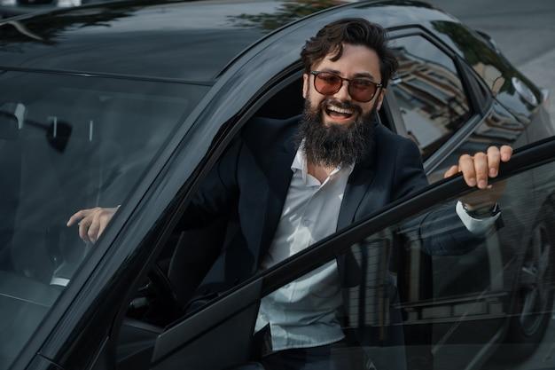 Portret stijlvolle, knappe man in de buurt van auto buitenshuis