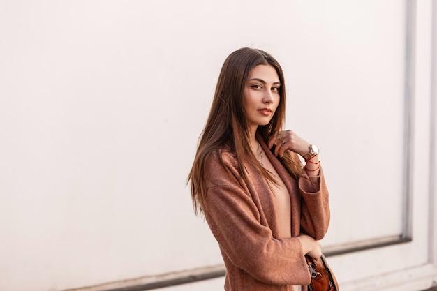 Portret stijlvolle mooie jonge vrouw met lang haar in elegante beige jas in de buurt van vintage witte muur. modieus aantrekkelijk schattig meisje mannequin in trendy bovenkleding poseren in de stad. lente stijl.