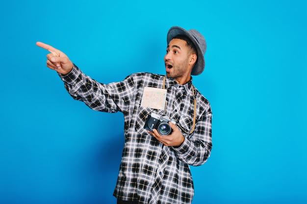 Portret stijlvolle verrast knappe jongen met camera, kaart, in hoed met plezier. reizen, genieten van vakantie, weekends, positiviteit uiten, reizen.