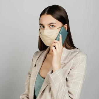 Portret stijlvolle vrouw met masker met behulp van mobiel