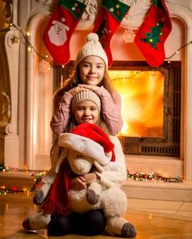 Portret tegen de open haard van lachende meisjes die op de vloer zitten met speelgoedschaapjes