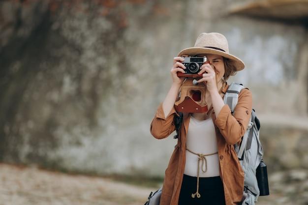 Portret tiener die voor camera stelt die foto met rotsen neemt