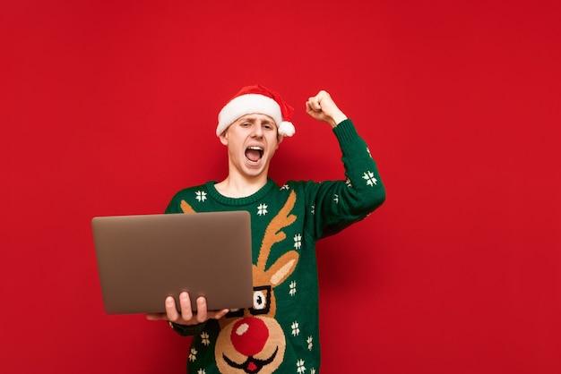 Portret tiener jongen met kerst trui met laptop