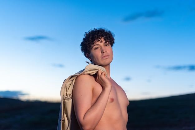 Portret tijdens de schemering van een niet-binaire man met naakte torso die naar de camera kijkt en een shirt vasthoudt
