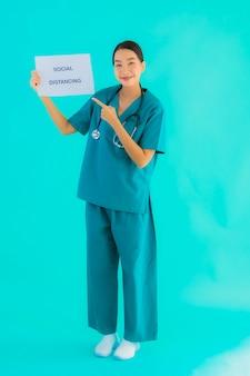 Portret toont de mooie jonge aziatische artsenvrouw teken met het sociale distantiëren