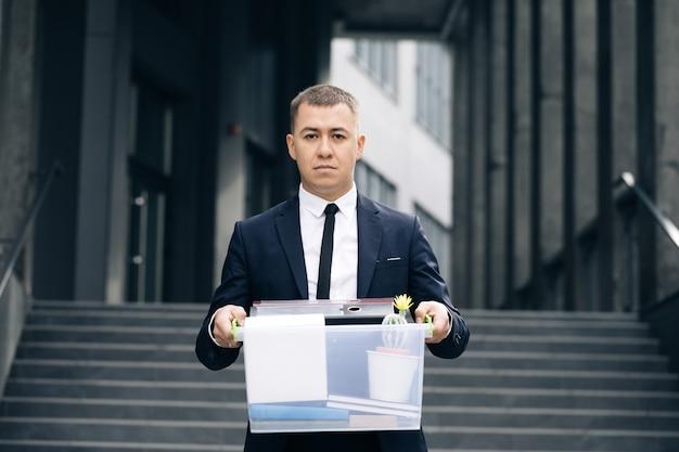 Portret triest mannelijke kantoormedewerker in depressie met doos met persoonlijke spullen