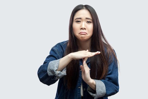 Portret triest van mooie brunette aziatische jonge vrouw in casual blauw denim jasje met make-up staan en kijken naar camera met time-out teken. indoor studio opname, geïsoleerd op lichtgrijze achtergrond.