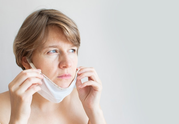 Portret trieste natuurlijke vrouw die een medisch masker draagt vanwege de coronavirus-epidemie.