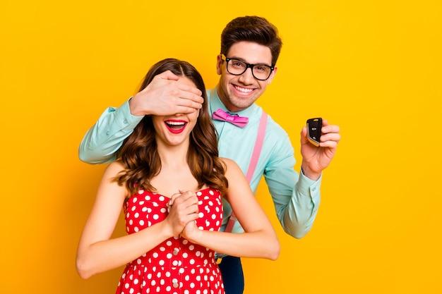 Portret twee mensen geek man verberg ogen geliefde vrouw geef cadeau sleutels koop auto