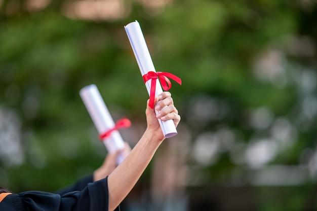 Portret twee vrouwelijke afgestudeerden, universitair afgestudeerden met een diploma en zijn gelukkig